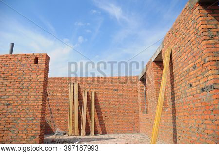 An Inside View From An Incomplete Brick House Construction With Built Walls And The Blue Sky Instead