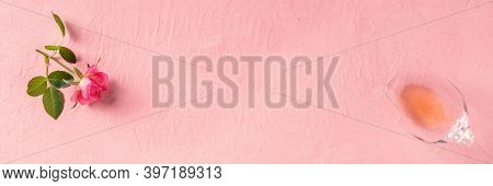 Romantic Panoramic Banner With Copy Space. A Pink Rose And A Glass Of Rose Wine, Shot From Above On