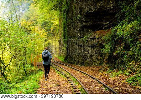 Rear View Of A Young Hiking Tourist Girl Enjoying Amazing Beauty Of Nature. Excursion On Old Narrow