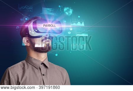 Businessman looking through Virtual Reality glasses with PAYROLL inscription, new business concept