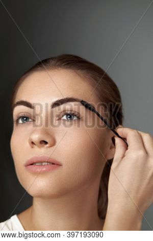 Eyebrow Makeup.  Beauty Model Shaping Brows With Brush Eyebrow Closeup . Beautiful Sexy Woman With P