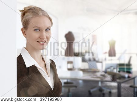 Woman portrait - portrait of young Entrepreneur woman. Designer and small business owner in fashion design studio. Lensflare.
