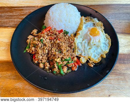 Rice Topped With Stir-fried Pork And Basil With A Fried Egg On The Table