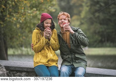 Man And Woman Having Coffee In The Autumn Park