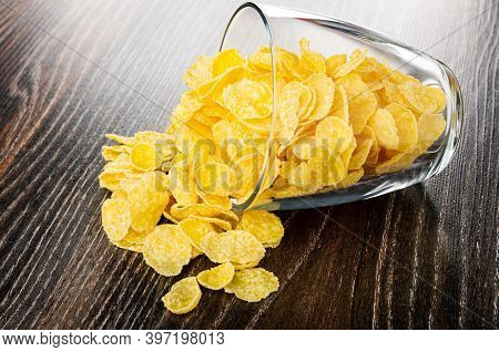 Overturned Transparent Glass With Glazed Corn Flakes On Dark Wooden Table
