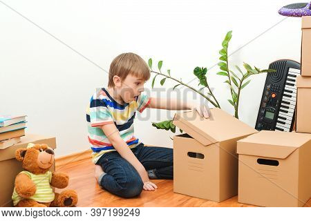 Happy Boy Having Fun In Moving Day To A New House. Housing A Young Family With Kid.