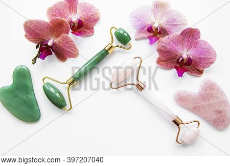Face Massage Jade Rollers And Orchid Flowers   On White Background