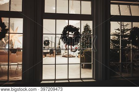 Christmas Tree And Decoration In The Window Background. Night Scene With A Snow And Brightly Decorat