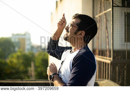 Over The Shoulder Shot Of Young Indian Man Flying A Kite By Pulling On The Thread On The Festival Of