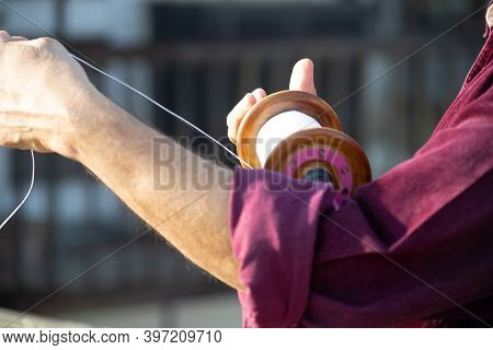 Slow Motion Shot Of Man Holding A Charki Phirki Thread Spool In The Crook Of His Elbow And Winding I