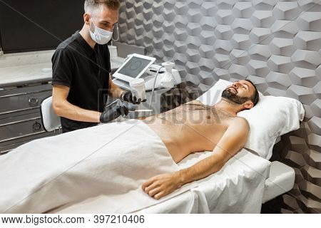Man With A Doctor At Luxury Spa Salon. Preparation For Liposuction Procedure