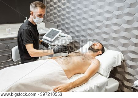 Man During An Ultrasound Liposuction Procedure At Luxury Spa Salon. Doctor Working On Abdomen Area