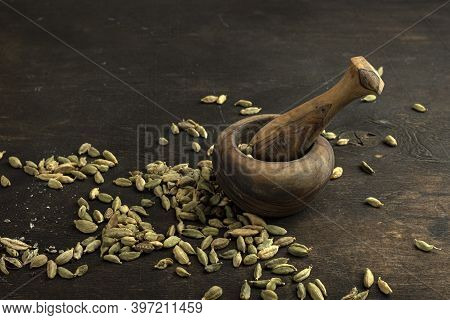 Cardamom , In A Wooden Mortar On A Wooden Background