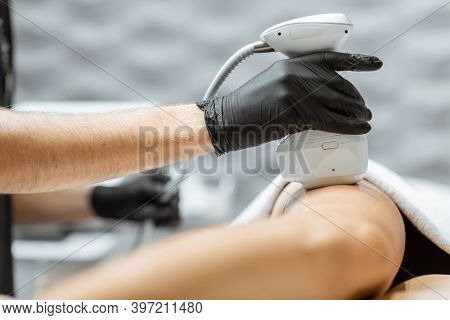 Young Woman During An Ultrasound Liposuction Procedure At Luxury Spa Salon. Doctor Working On Thigh