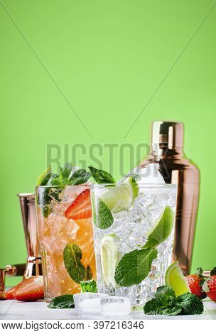 Fresh Mojito Cocktail Set With Lime, Mint, Strawberry And Ice In Glass On Green Background. Summer C