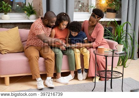 Young African family of father, mother, son and daughter with tablet sitting on couch against window in living-room and watching movie