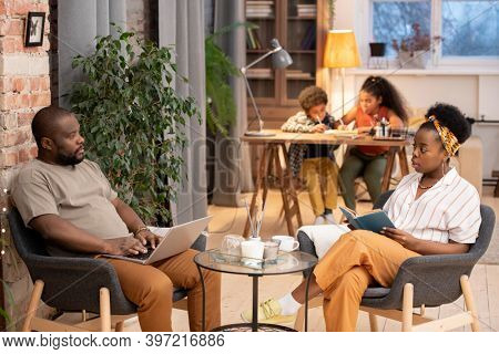 Young African woman with open book and her husband with laptop sitting in grey armchairs by small table while their kids doing homework