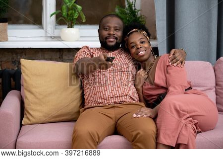 Happy young affectionate African husband and wife sitting on couch against window in living-room and watching tv program or movie