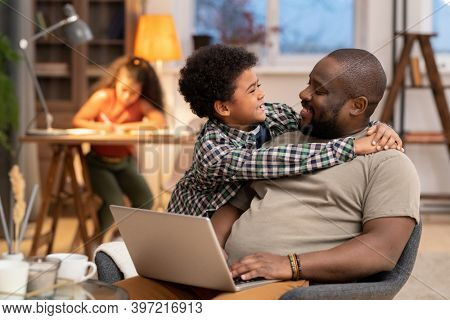 Happy affectionate African boy embracing his father sitting in armchair and networking in front of camera against daughter doing homework