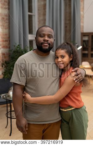 Happy African girl with toothy smile embracing her father while both standing in front of camera on background of window and furniture