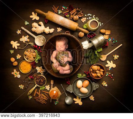 Newborn baby sleeping in a bowl surrounded by the ingredients for gingerbread Christmas cookies
