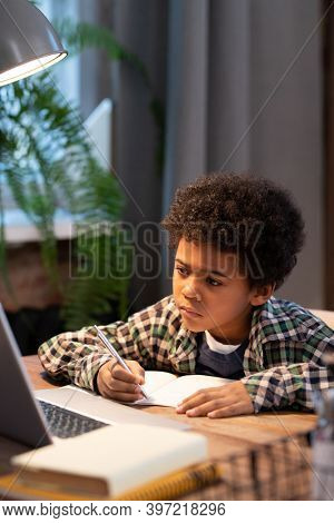 Serious African schoolboy making notes in copybook while sitting by table in front of laptop and looking at display during online lesson
