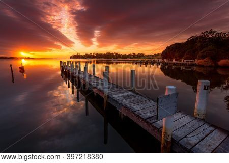 Old Weathered Timber Jetty Pointing Towards The Sunrise With Pretty Reflections In The Water. Mallac