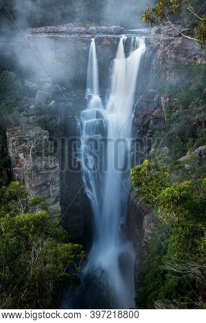 Enchanting Carrington Falls With Strong Flows Cascading Over Tall Cliff With Wind Blowing Trees And