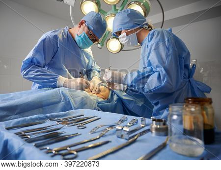 Doctor And Assistant Performing Aesthetic Surgery In Operating Room With Various Stainless Steel Too