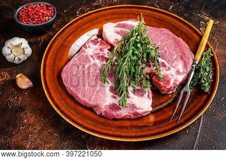 Fresh Raw Pork Loin Steaks From Neck Meat. Dark Background. Top View
