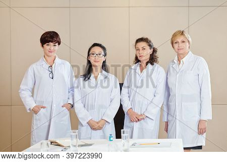 Group Of Positive Female Researches In Labcoats Standing At Table After Conforence On New Coronaviru