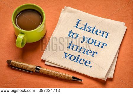 listen to your inner voice - inspirational handwriting on a napkin with a cup of coffee, confidence, intuition and personal development concept
