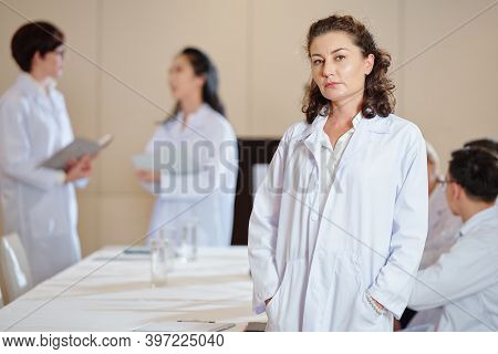 Serious Mature Female Pharmacologist In Labcoat Standing At Table In Boardroom And Looking At Camera
