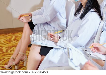Cropped Image Of Female Doctor Taking Notes On White Sheet When Attending Conference For Medical Wor