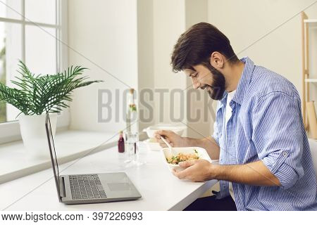 Busy Young Man Eating Takeaway Food During Lunch Break At Home Or In The Office