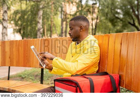 Young courier of African ethnicity with orders in big red backpack using touchpad to look through addresses of clients while sitting on bench
