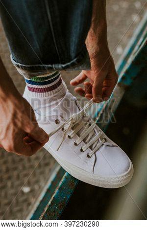 Man fixing shoelaces on white sneaker