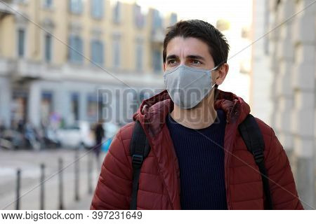 Young Man Wearing Face Mask Walking Down The Street Looking To The Side