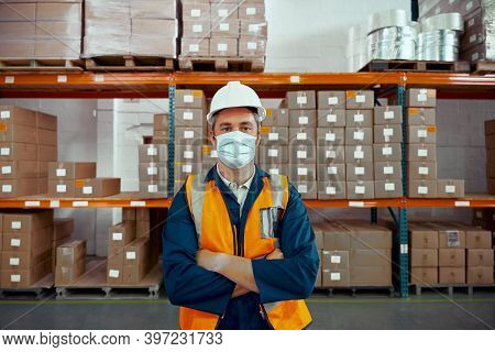 Portrait Of A Confident Factory Male Worker Wearing Protective Helmet And Mask Standing In Front Of