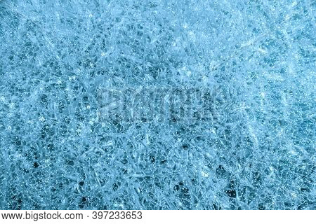 Blue Cracked Ice Background. Frozen Water, Sea. Frosty Winter Texture. Macro Shot.