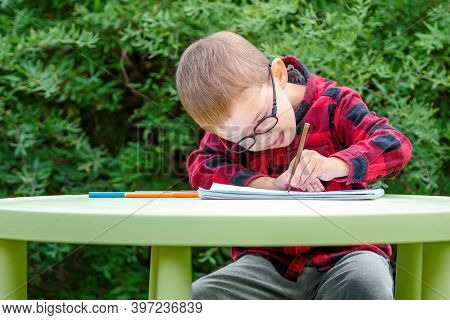 A Little Boy Draws In The Garden. He Wears Glasses And An Eye Patch (occluder) To Prevent Amblyopia