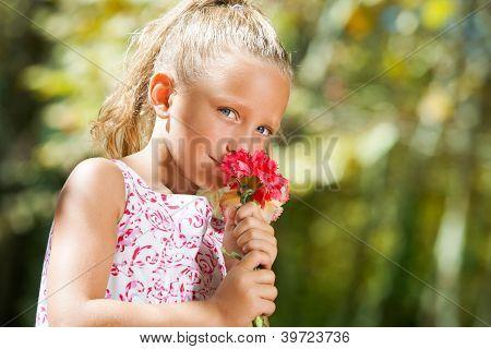 Blue Eyed Girl Smelling Flower Outdoors.