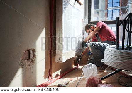 Side View Of Male Heating Engineer In Work Overalls Using Electric Drill While Laying Pipes On The F