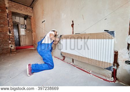 Plumber In Work Overalls Using Wrench While Installing Heating Radiator In Room. Man In Helmet Insta