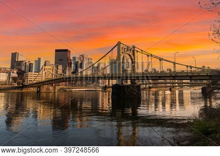 Urban waterfront and bridges crossing with sunset sky in downtown Pittsburgh, Pennsylvania.
