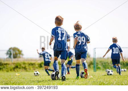 Children Running After Balls On Soccer Training Camp. Kids Practicing Football On Grass Field. Schoo
