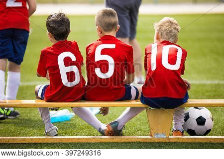 Kids Soccer Team On Wooden Bench. Substitute Football Players Waiting On Sideline. Children Making S