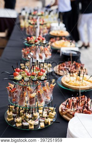 A Set Of Canapes And Snack At A Banquet With Black Table. Slices Of Tomato, Cucumber, Olive, Cheese,