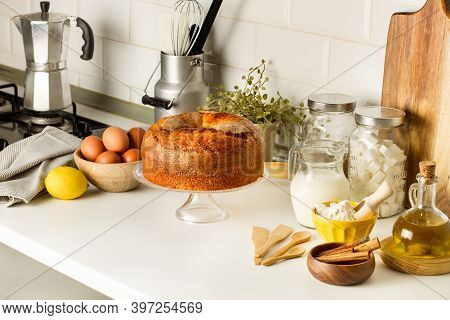 A Vanilla Cake And Ingredients On A Cake Stand On The Kitchen Countertop