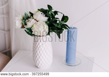 Small Bouquet Of Fresh Flowers, White Peonies And Greenery In Vase And Candle. Wedding Flowers, Brid
